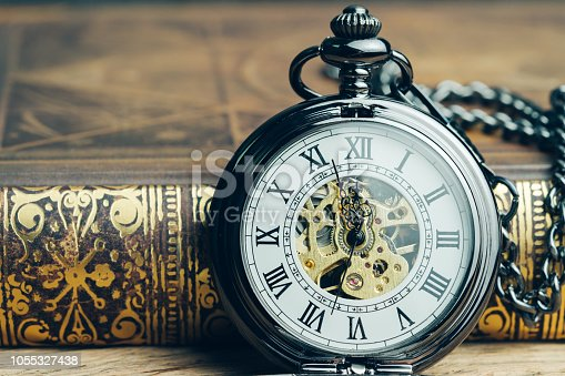 Time running, deadline, life time or business milestone concept, closed up vintage pocket watch or clock on book in vintage tone.