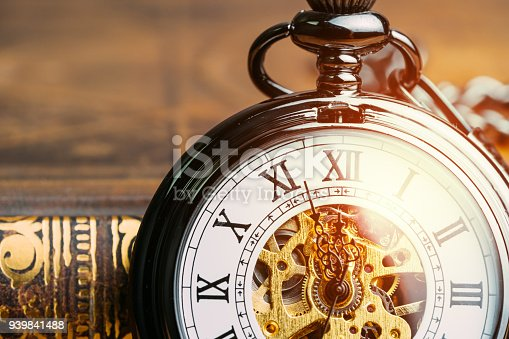 istock Time running symbol or business deadline concept, closed up vintage pocket watch on book with golden artificial light 939841488