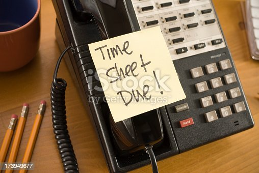 Urgent Time Sheet Notice on a business telephone handset