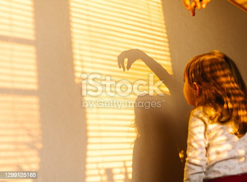 Time spent during quarantine. Sun and shade. Little girl in pajamas at home playing with the sun on the wall. Photo from behind. High quality photo