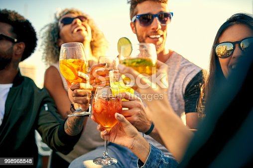 Shot of a group of young friends hanging out and having drinks together outdoors