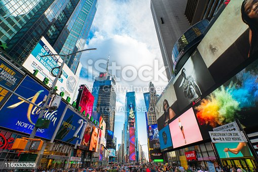 981808424 istock photo Time Square, New York City. Skyscrapers Against Beautiful Cloudy Sky. Billboards, Neon Art and Tourists 1160332629