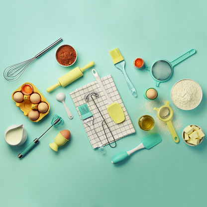 istock Time to bake. Baking ingredients - butter, sugar, flour, eggs, oil, spoon, rolling pin, brush, whisk, towel over blue background. Bakery food frame, cooking concept. Top view, copy space. Flat lay 1146957546