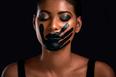 Studio shot of a young woman with a hand painted on her mouth posing against a black background