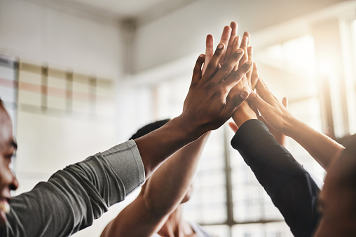 Shot of a group of young people giving each other a high five during their workout in a gym