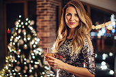 Close up of woman holding glass of champagne. Woman wearing sparkly elegant dress. Evening or night with Christmas tree in background. Looking at camera.