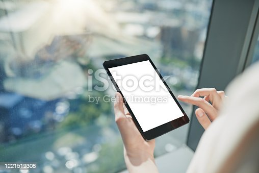 Shot of a unrecognizable person browsing on a digital tablet with the city in the background