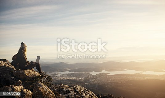 Shot of a young hiker using her laptop while sitting on top of a mountain