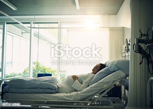 Shot of a tired young woman lying down on a bed and resting inside of a hospital