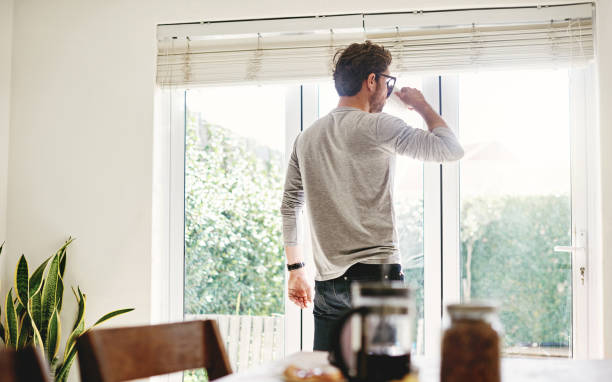 Time to contemplate the day ahead Shot of a young man having a cup of coffee while looking out of the window at home bachelor stock pictures, royalty-free photos & images