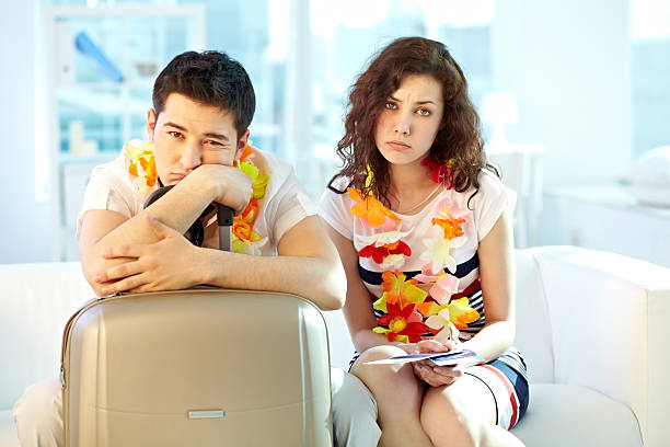 Time to depart Portrait of a sad couple of travellers going to depart depart stock pictures, royalty-free photos & images
