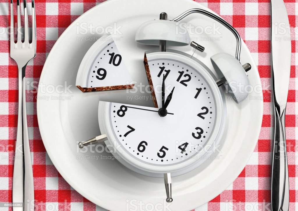 Time to eat concept, cut clock on plate stock photo