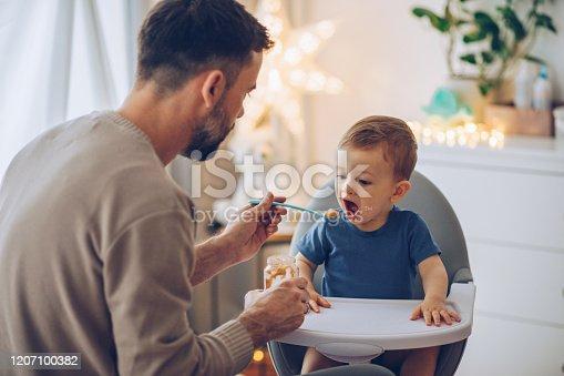 Father feeding baby boy in high chair