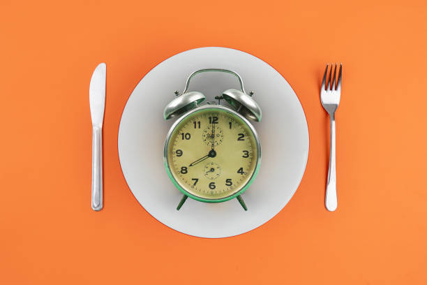 Time to eat with clock plate fork stock photo