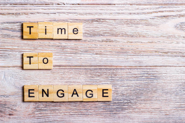 time to engage text on cubes on wooden background stock photo