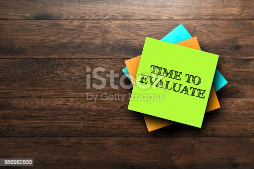 istock Time To Evaluate, the phrase is written on multi-colored stickers, on a brown wooden background. Business concept, strategy, plan, planning. 956962830
