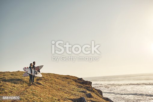 Shot of a young couple walking up a cliff at the beach with their surfboards