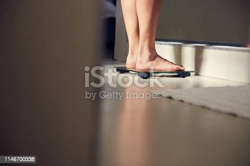 Shot of an unrecognizble woman weighing herself on a scale at home