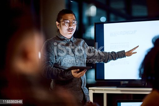 Shot of a young businessman delivering a presentation during a late night meeting at work