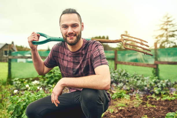 Time to get these green thumbs to work Portrait of a young man holding a pitchfork while working on a farm pitchfork agricultural equipment stock pictures, royalty-free photos & images
