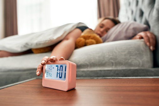 Young woman pressing snooze button on early morning digital alarm clock. Selective focus. Horizontal shot