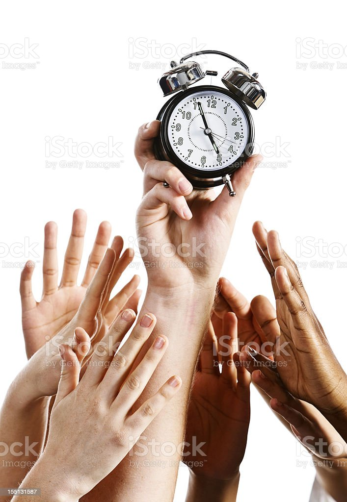 Time to go home: many hands grab alarm clock royalty-free stock photo