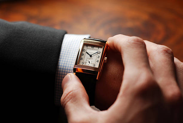 Time to go Businessman checking his wristwatch - nice shot over the shoulder. It's time to go to the next appointment. wristwatch stock pictures, royalty-free photos & images