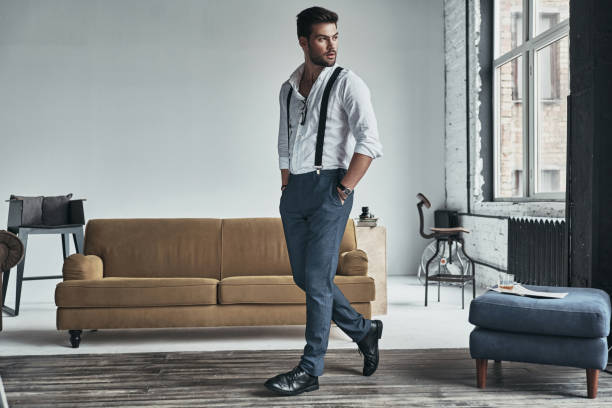 Time to go. Full length of handsome young man in white shirt and suspenders looking away and keeping hands in pockets while walking through the room suspenders stock pictures, royalty-free photos & images
