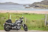 Scotland / United Kingdom - August 03, 2020: Grey vintage looking motorbike and view of beautiful beach with white sands and light blue waters in the background