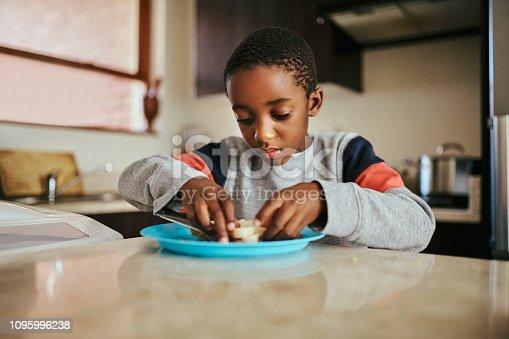 Shot of an adorable little boy eating a sandwich at home