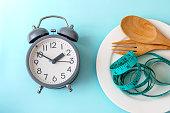コントロールやダイエットのコンセプトは、青の背景に健康ツール コンセプト装飾付き目覚まし時計を時間を食べて体重を失うまでの時間