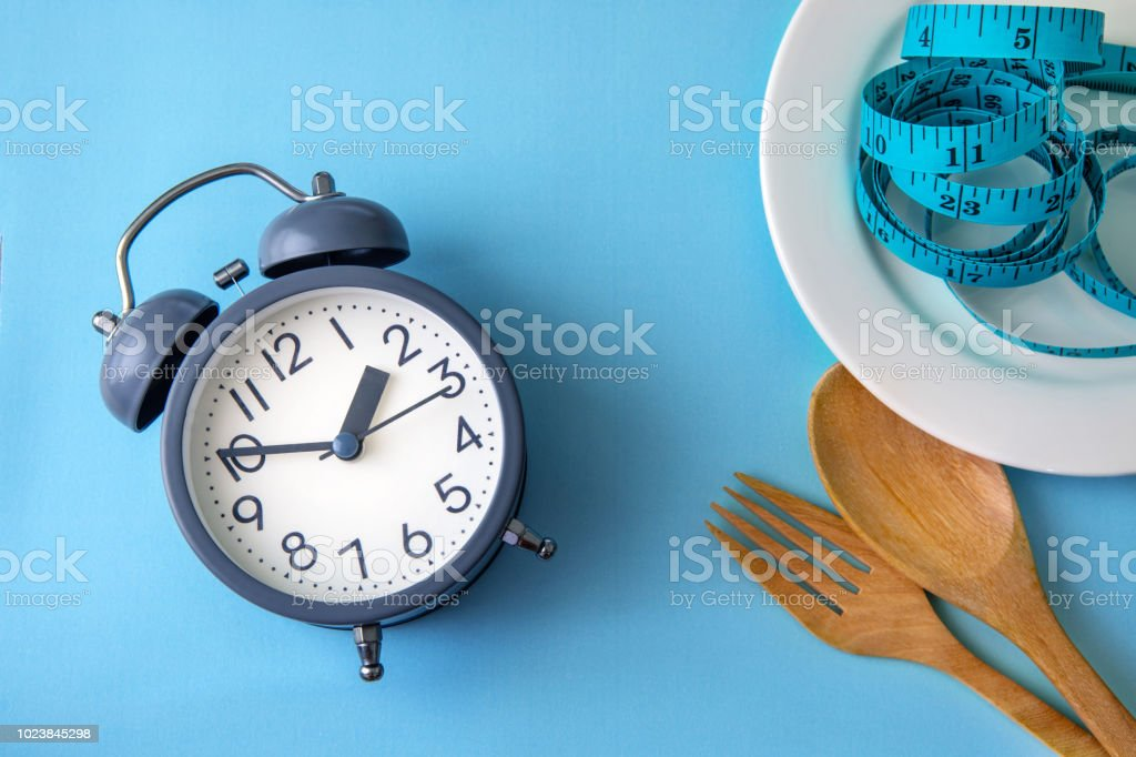 Time to lose weight , eating control or time to diet concept , alarm clock with a healthy tool concept decoration on blue background royalty-free stock photo