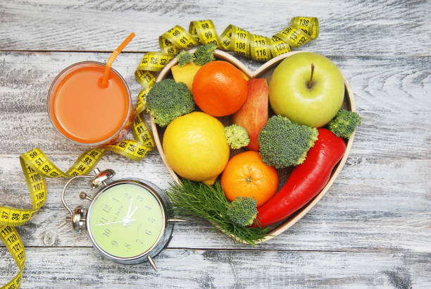 Time to lose Weight. Fruit, Vegetable on Wooden Heart Shape box and Alarm Clock on the table, Diet and Fitness concept. Time to lose Weight. Fruit, Vegetable and Alarm Clock on the table, Diet and Fitness. hypertensive stock pictures, royalty-free photos & images