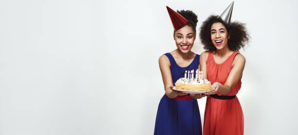 zeit, einen wunsch zu machen! breites foto von fröhlichen jungen afro-amerikanischen frauen in partyhüten, die einen kuchen mit kerzen halten, während sie geburtstag feiern - marinekuchen stock-fotos und bilder