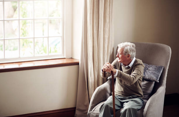A time to pause and reflect Shot of a senior man looking thoughtfully out of a window at home fragility stock pictures, royalty-free photos & images