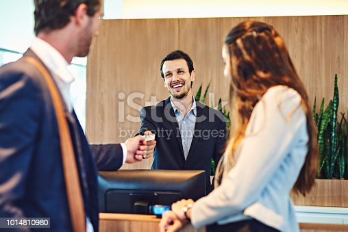Cropped shot of a businessman and businesswoman checking into a hotel