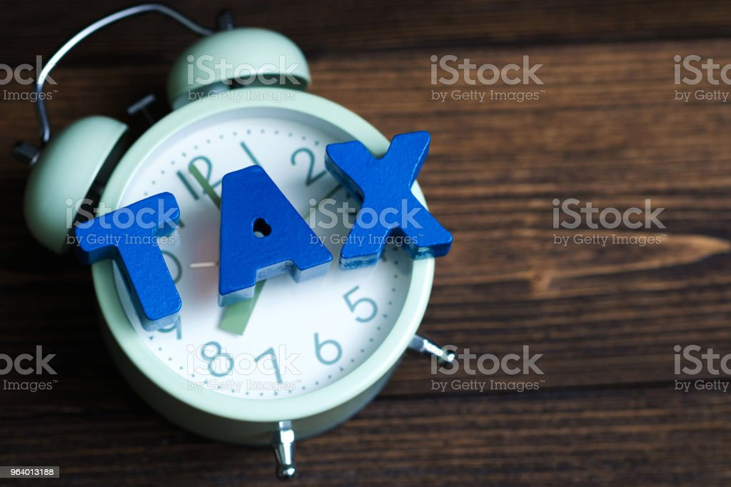 Time to pay TAX concept. TAX alphabet and vintage alarm clock on wooden working table in dark background, business and financial concept. - Royalty-free Accountancy Stock Photo