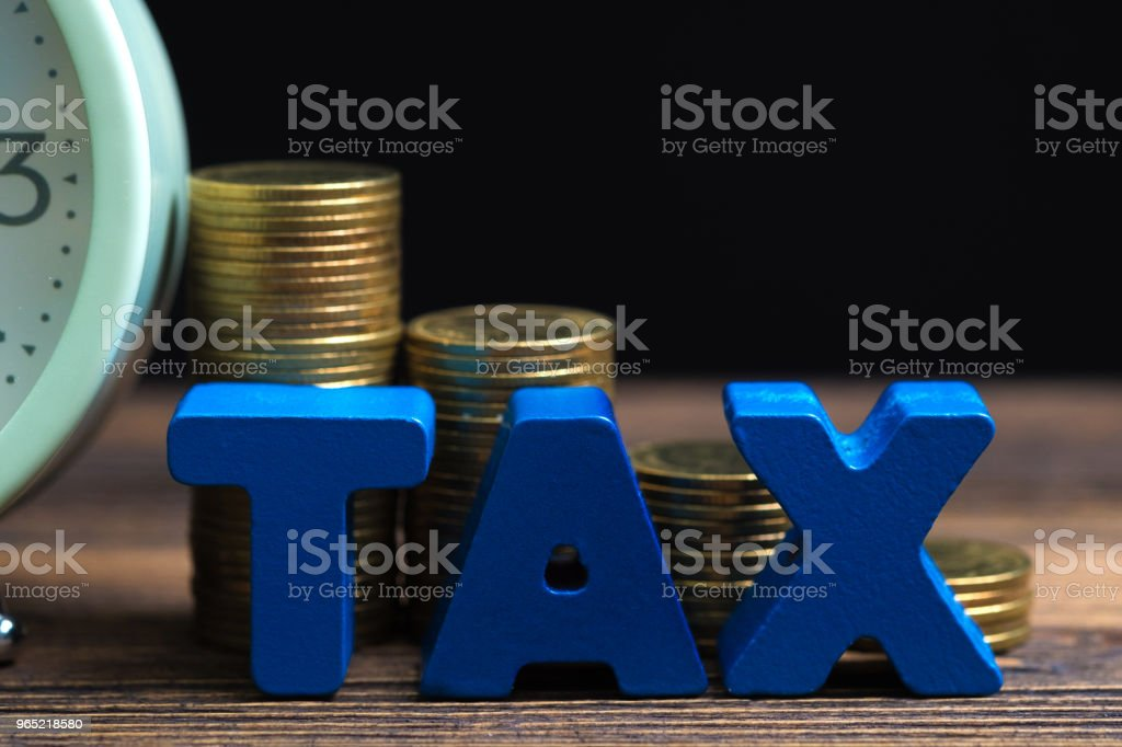 Time to pay TAX concept. TAX alphabet with stack of coin and vintage alarm clock on wooden working table in dark background, business and financial concept. royalty-free stock photo