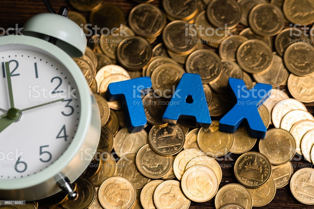 Time to pay TAX concept. TAX alphabet with stack of coin and vintage alarm clock on wooden working table in dark background, business and financial concept. zbiór zdjęć royalty-free