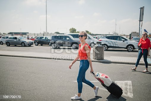 One happy young woman is crossing the airport parking lot with her baggage, looking happy to finally have arrived.