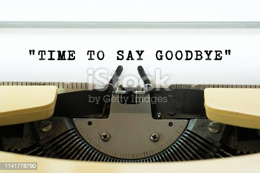 Time to say goodbye word typed on a yellow vintage typewritter. Business concept.