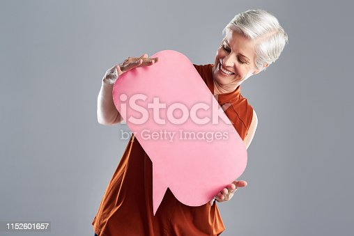 Shot of a cheerful mature woman holding a speech bubble against a grey background