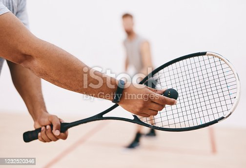 Cropped shot of a man serving a ball with a racket during a game of squash