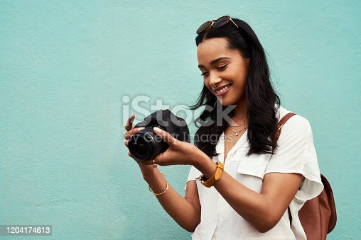 Cropped shot of an attractive young woman standing alone against a blue background in the city and holding her camera