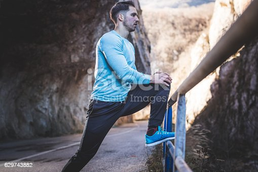 Young man stretching on the fence of the road and preparing for running