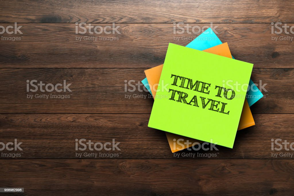 Time To Travel, the phrase is written on multi-colored stickers, on a brown wooden background. Live concept stock photo