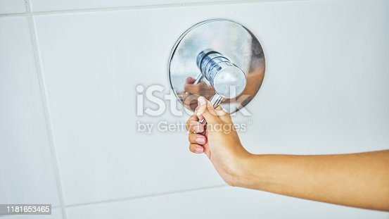 Cropped shot of an unrecognizable woman holding a shower mixer tap inside her shower at home