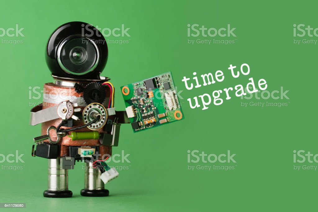Time to upgrade concept. Robot with abstract circuit chip. retro style toy character with funny black helmet head. Copy space, green background stock photo