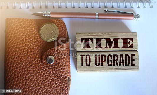 time to upgrade text on a wooden blocks, brown leather wallet, coins and pen put on copybook. Business technologies project concept.