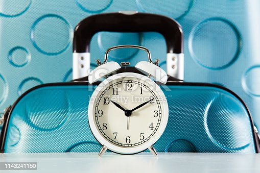 Time to vacation concept. Vacation trip background. White alarm clock and blue suitcase.